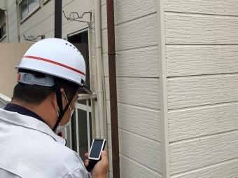 屋根の状態を手元カメラで確認する作業員