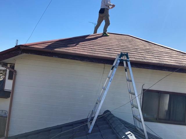 下屋根に脚立を掛け、上屋根に登るスタッフ