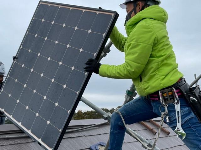 屋根上で撤去した太陽光パネルを受け渡す作業員