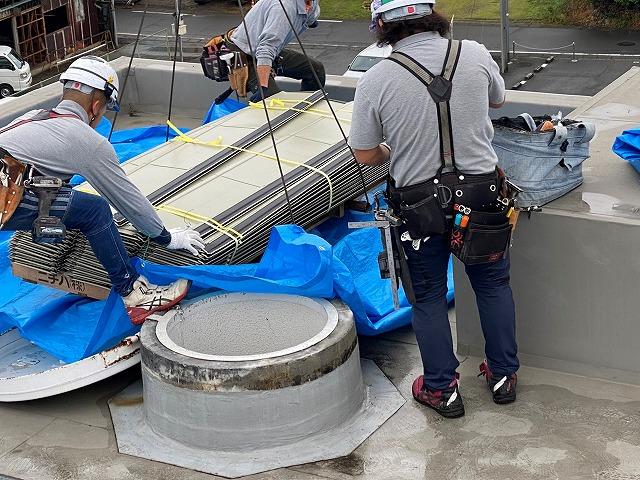 クレーンで吊り上げられた屋根資材を、屋上で受け取る職人