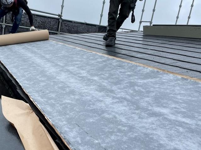 粘着式防水シートをカラーベスト屋根材に施工する職人