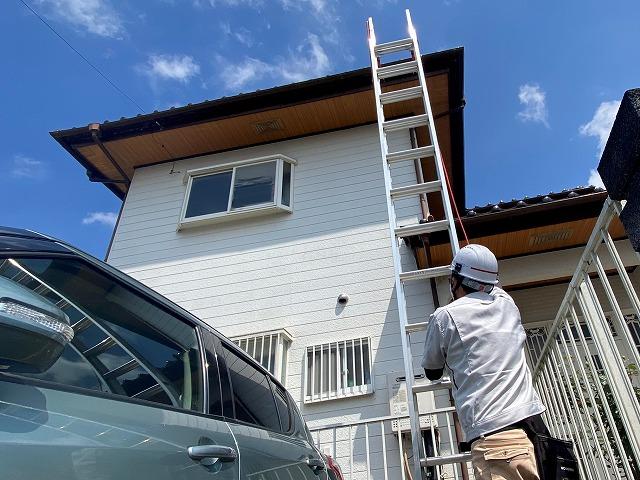 二階の屋根に梯子を設置するスタッフ