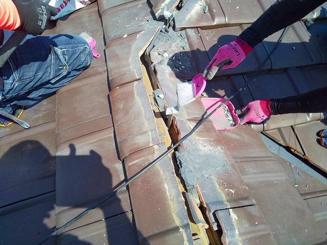 解体した棟付近を清掃をする屋根職人