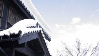雪が屋根に積もり今にも雨樋に落ちそうになっている