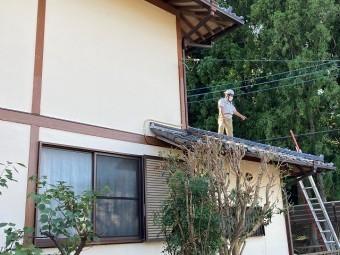 瓦屋根の不具合部を屋根の上から確認するスタッフ