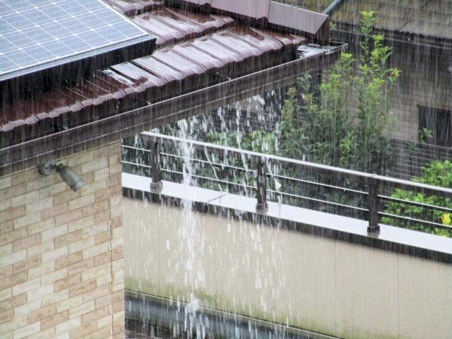 豪雨により雨が雨樋から飛び出している