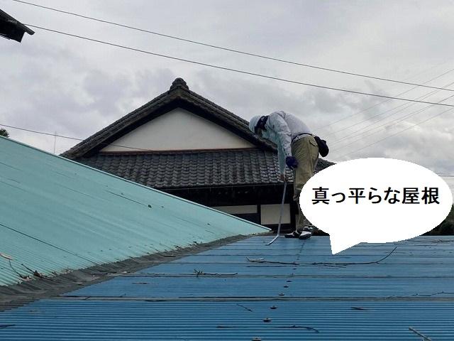 雨漏りしている平らな屋根に登って調査するスタッフ