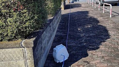 散水調査のために、敷地内にドラムホースを這わせる