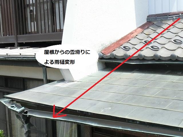 屋根からの落雪で損傷した玄関先の銅雨樋