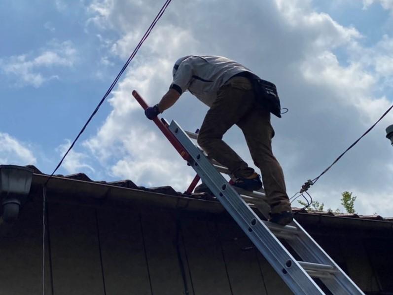 ハシゴの手すりを伸ばし屋根に登る作業員
