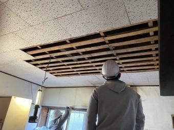 天井材を剥がし屋根下地部を見上げる職人