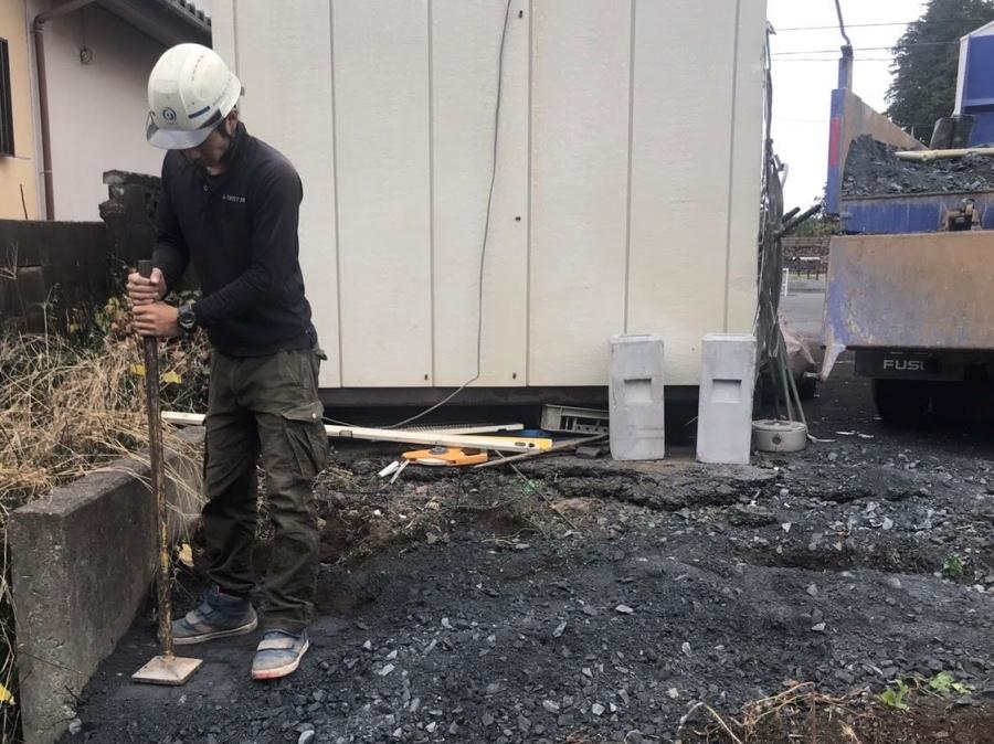 外構設置の為に、土台の砕石を固める職人