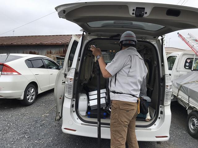 屋根調査の為に高所カメラをセッティングする作業員