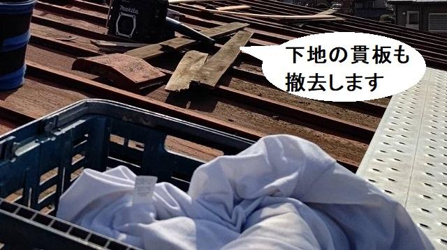 瓦棒屋根の棟木を解体する職人