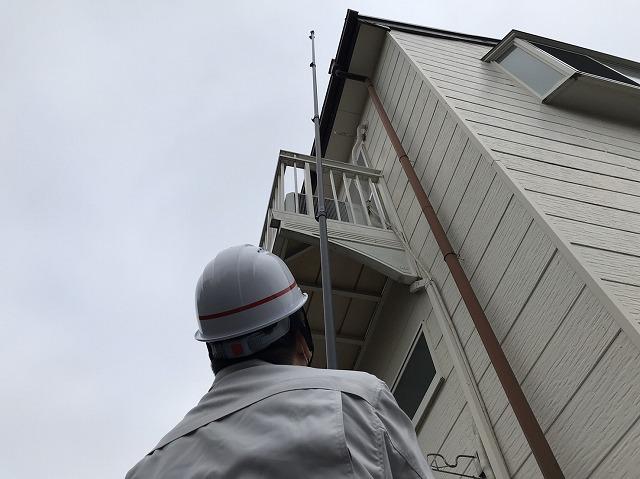 高所棒を伸ばし屋根の状態を撮影するスタッフ