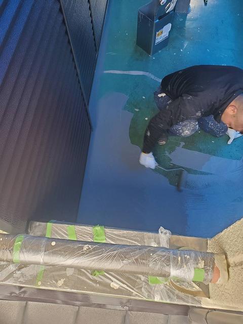 ウレタン防水の本材をローラーで塗布する職人