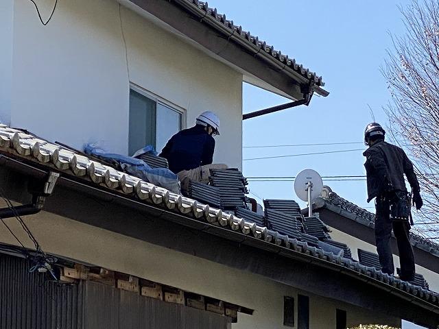 下屋根にて作業する職人