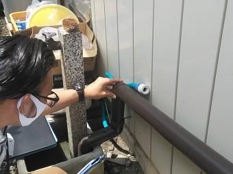 雨樋のジョイント部分に緩みが無いか確認する作業員