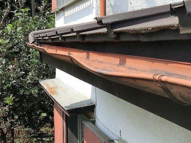 赤茶色の半丸雨樋が変形している