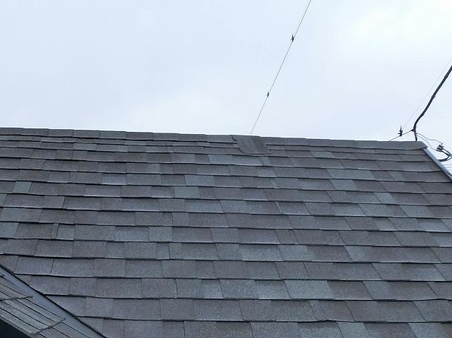剥がれたアスファルトシングル材が棟に飛んでいます