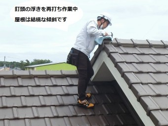 屋根の最も高い部分にある棟の浮き釘を打ち込む職人