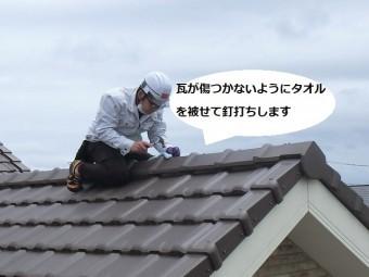 平板瓦屋根の棟部にまたがり棟の釘を打ち込む店長