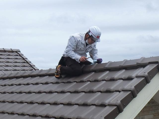 屋根にまたがり屋根修理を行う街の屋根やさん水戸店のスタッフ
