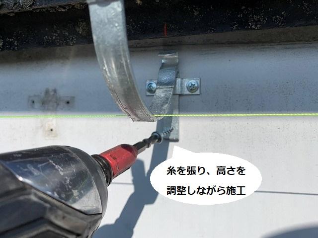 糸を張って高さを調整しながら雨樋用の支持金具を施工