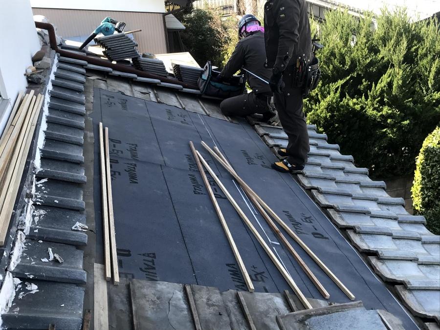 瓦屋根の部分葺き直し作業中の職人