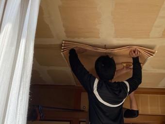 2人の職人が天井壁紙を貼る