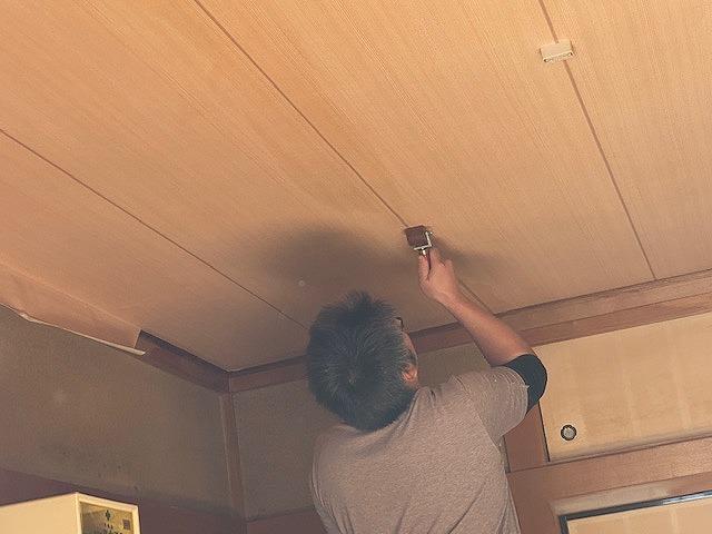 専用ローラーで天井壁紙を仕上げる職人