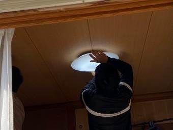 職人がシーリングライトカバーを設置している