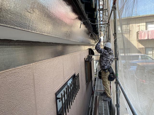 新しい軒樋をスライドさせ繋ぎ場所を確認する職人