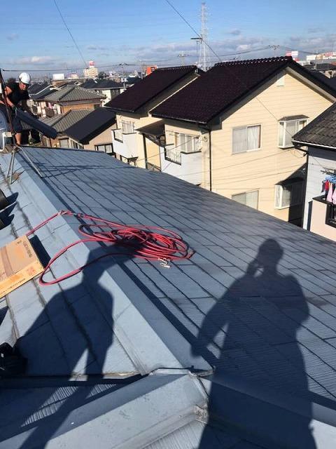 屋根に荷物を揚げる職人