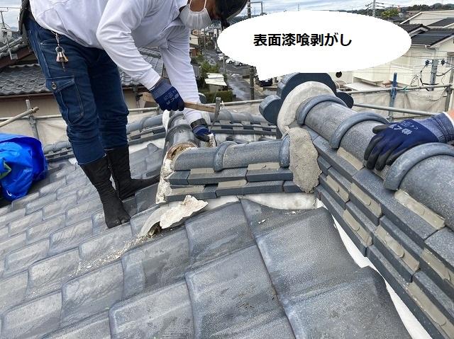 棟の表面に塗布された漆喰を剥がす職人