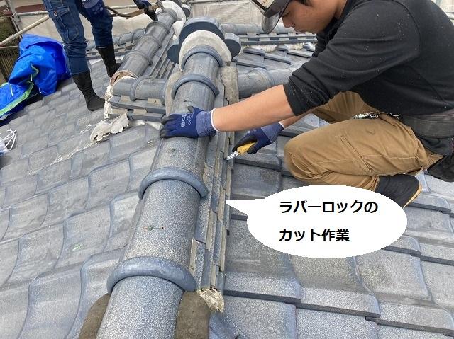 棟に施されたラバ―ロックをカッターで切る作業員