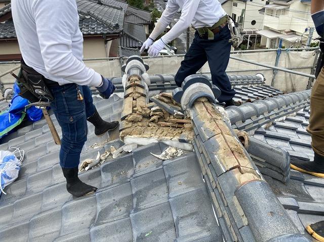 屋根工事の為、棟瓦を解体する二名の職人