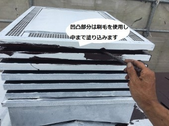 煙突の凹凸部に刷毛で塗り込む職人