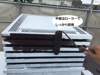 換気用煙突にローラーで遮熱塗料を塗布する職人