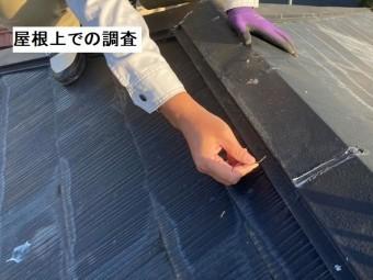 屋根上で、棟板金の釘留めの状態を確認するスタッフ