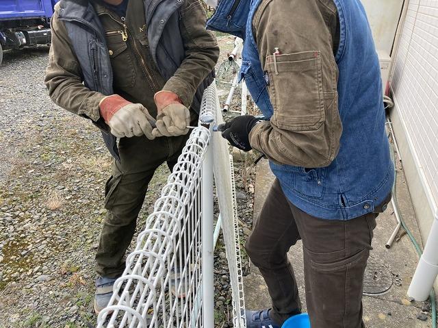 工具で外溝フェンスの解体を行う二名の職人