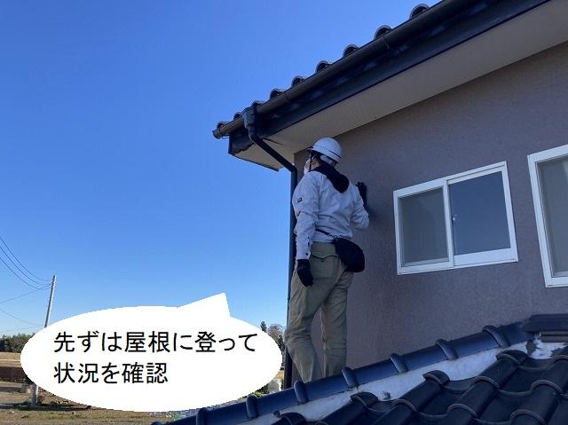下屋根に登って修理希望箇所を確認する調査スタッフ