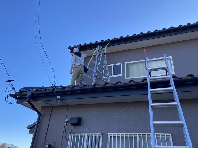 下屋根に伸縮脚立をかける調査スタッフ
