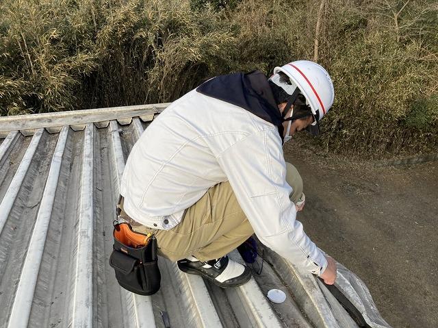 折板屋根の穴をパテで埋める職人
