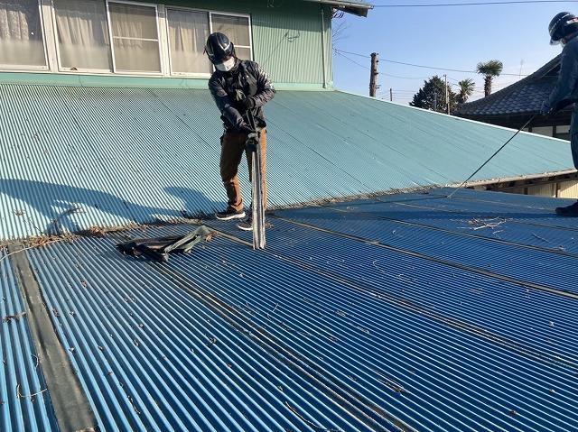屋根に応急処置された防水テープを剥がす職人
