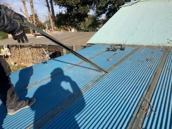 トタン波板に応急処置された防水テープを引っ張り剥がす職人