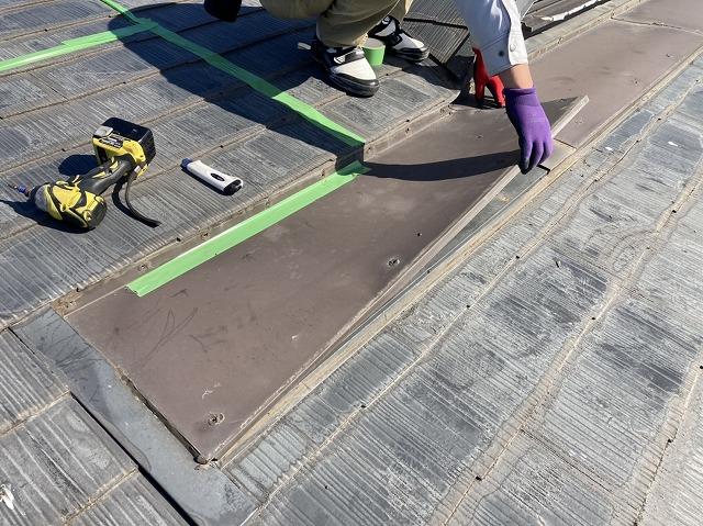 どぶ溝を塞いでいる鉄板を外すスタッフ