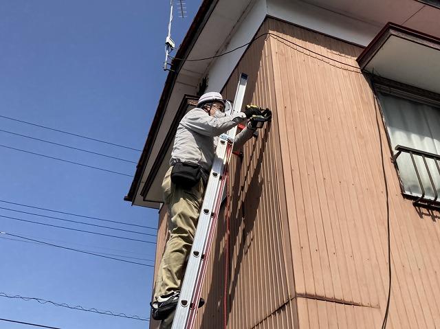 トタン外壁に梯子を掛け、ビスを打ち増しするスタッフ