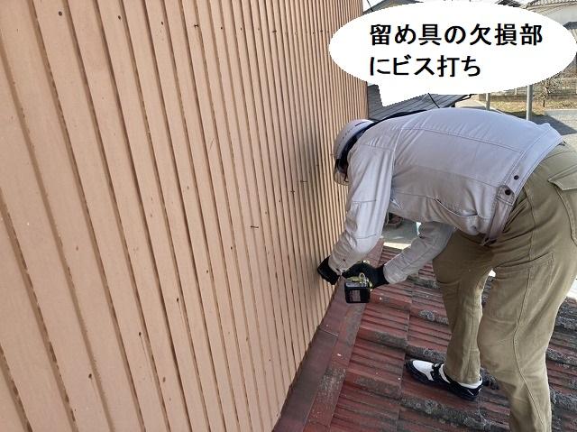 外壁トタンの留め具欠損部にビスを打つ作業員