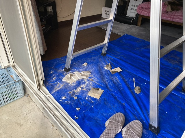 天井材の穴開け時に養生したブルーシートに落ちた石膏ボードの破片